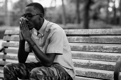 African American Man Praying On Bench