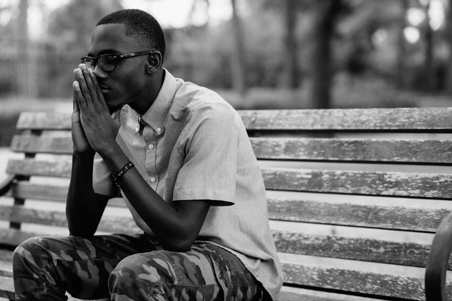 African American Man Praying On Bench