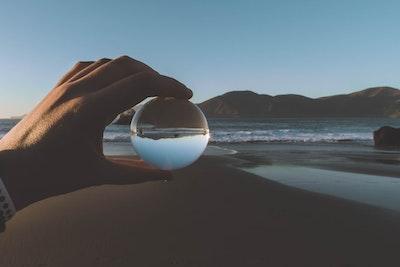 Hand Holding Glass Ball Sea