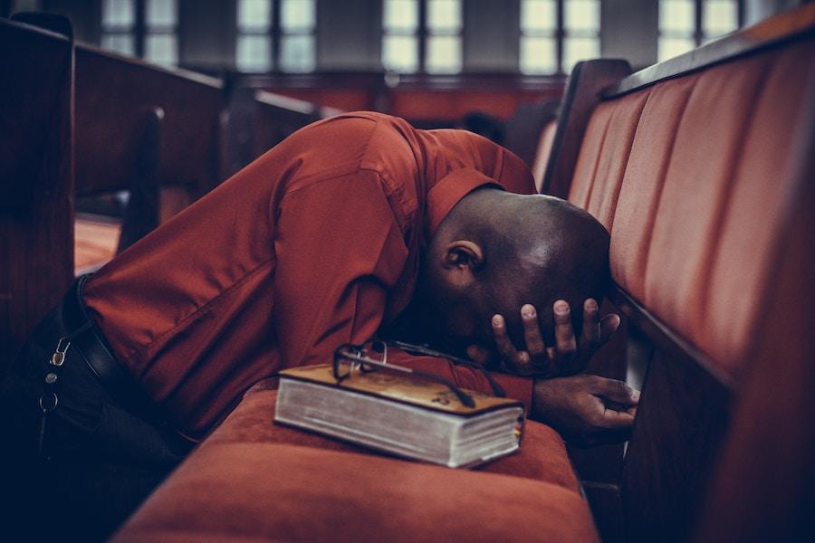 Man Kneeling Praying On Pew