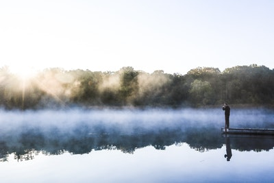 Man Reflecting Over Morning Lake