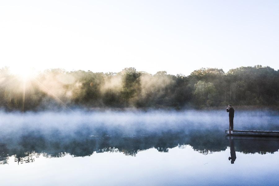 Man Reflecting Over Morning Lake