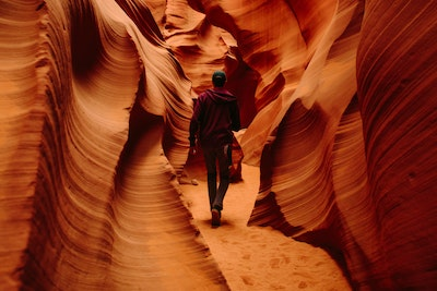 Man walking through red canyon
